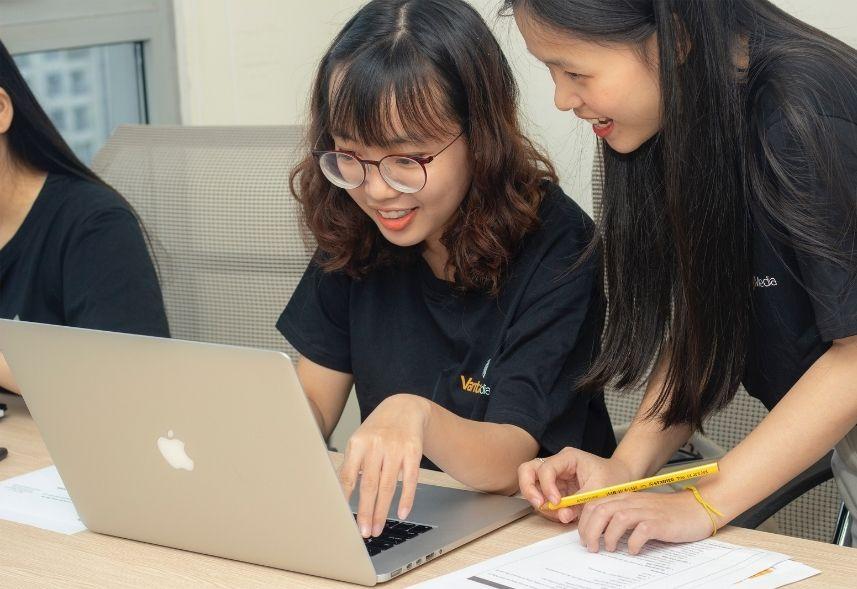 analista de midias sociais: imagem de duas meninas olhando para a tela de um notebook conversando entre si