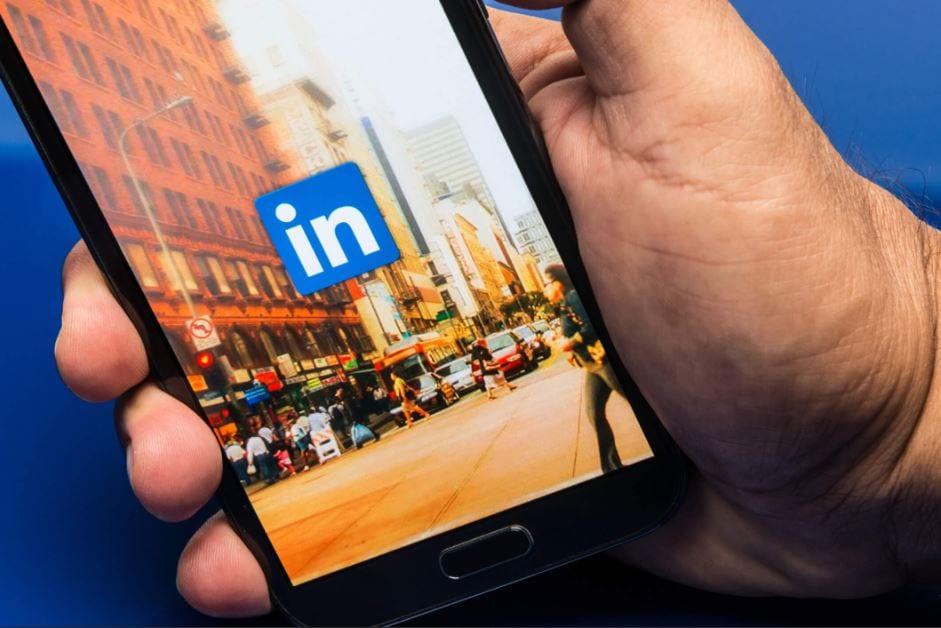 algoritmo do linkedin: imagem de uma mão segurando um celular com a tela do linkedin aberta