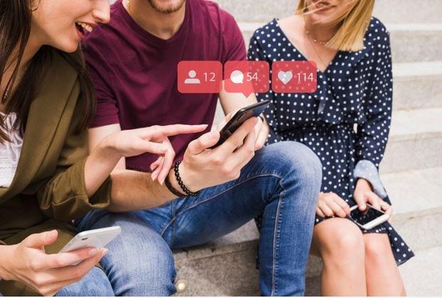 Seguidores falsos no Instagram: imagem de três pessoas interagindo com um celular.