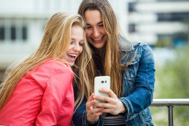 Como usar gifs: imagem de duas pessoas sorrindo olhando para o celular.