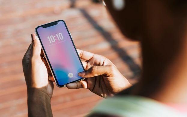 Contagem Regressiva do Instagram: imagem de uma pessoa olhando a hora, na tela de um celular.