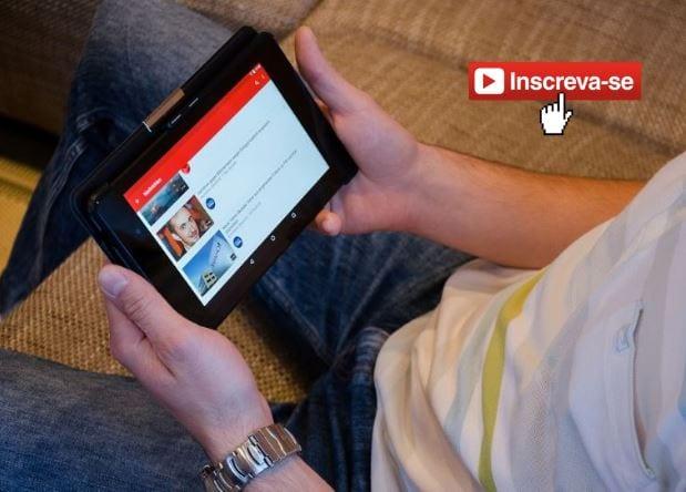 Como ganhar inscritos no YouTube: imagem de uma pessoa, sentada no sofá, segurando um tablet assistindo vídeo no YouTube.