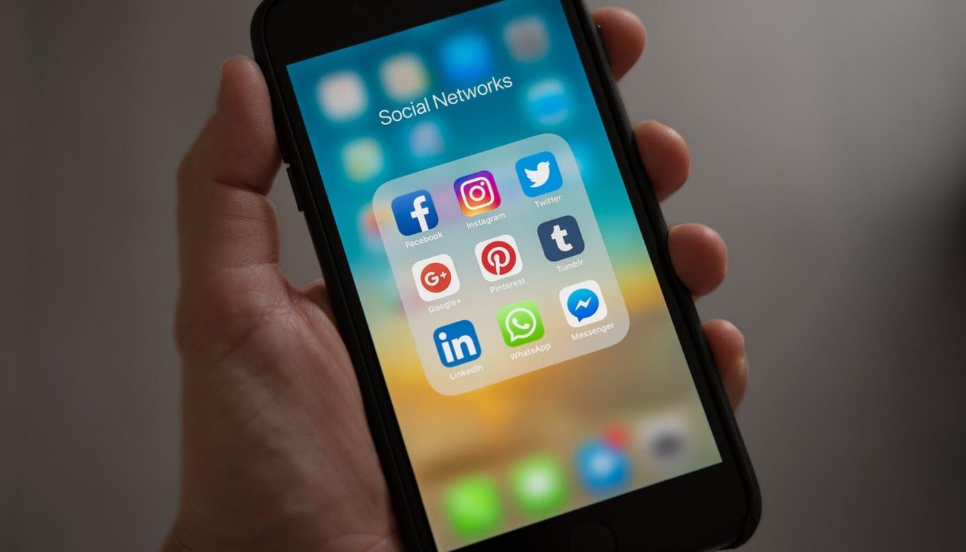 Canal de atendimento: imagem de uma mão segurando um iphone com a tela das redes sociais aberta.