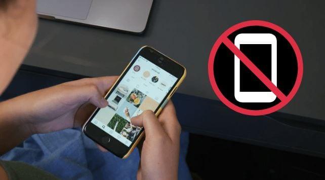 Ação bloqueada no Instagram: imagem de uma pessoa mexendo no Instagram e o ícone de bloqueio