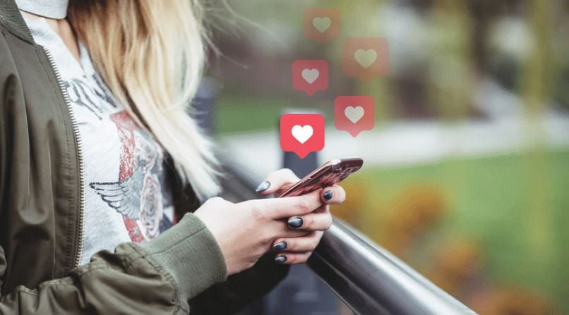 Likes ocultos no Instagram: imagem de uma mulher loira segurando o celular com as duas mãos e os likes saindo da tela desaparecendo no ar.