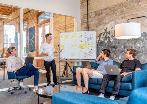 Branding Pessoal: imagem de quatro pessoas fazendo uma reunião com um quadro e post-its colados