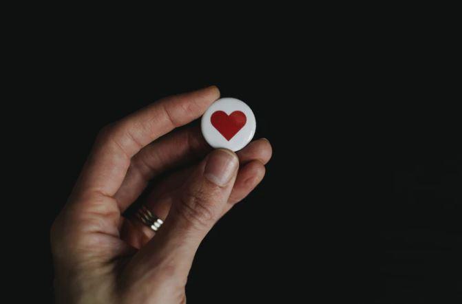Prova Social: imagem de uma mão segurando um botão de coração
