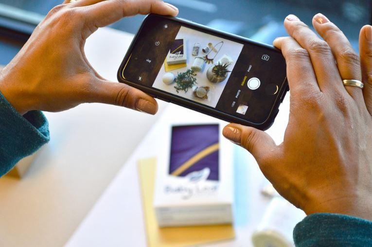 Anúncios nos Stories do Instagram: imagem de duas mãos segurando o celular tirando foto de uma mesa cheia de produtos