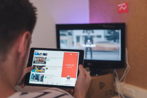 Ganhar visualizações no YouTube: imagem de um homem com um tablet nas mãos procurando vídeos no YouTube .