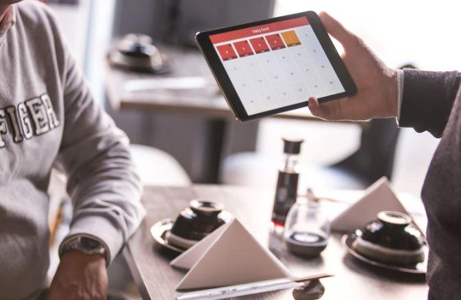 Calendário de Marketing: imagem de duas pessoas em reunião, uma delas está segurando um tablet com a tela aberta em um calendário online