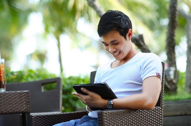 Redes Sociais Novas: imagem de um jovem sentado ao ar livre, segurando um tablete e sorrindo e olhando para a tela.
