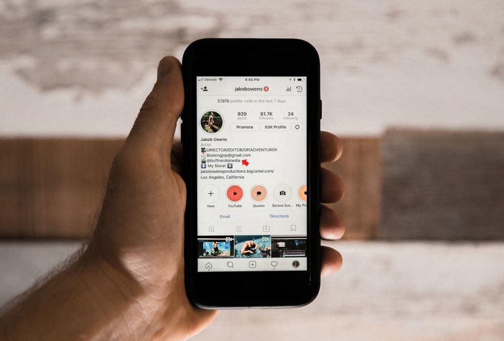 Link na Bio: imagem de uma mão segurando um celular com a página de um perfil do instagram na tela