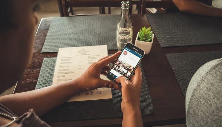 Deixar de seguir no Instagram: imagem de duas mãos segurando um celular sob a uma mesa com a tela do Instagram aberta