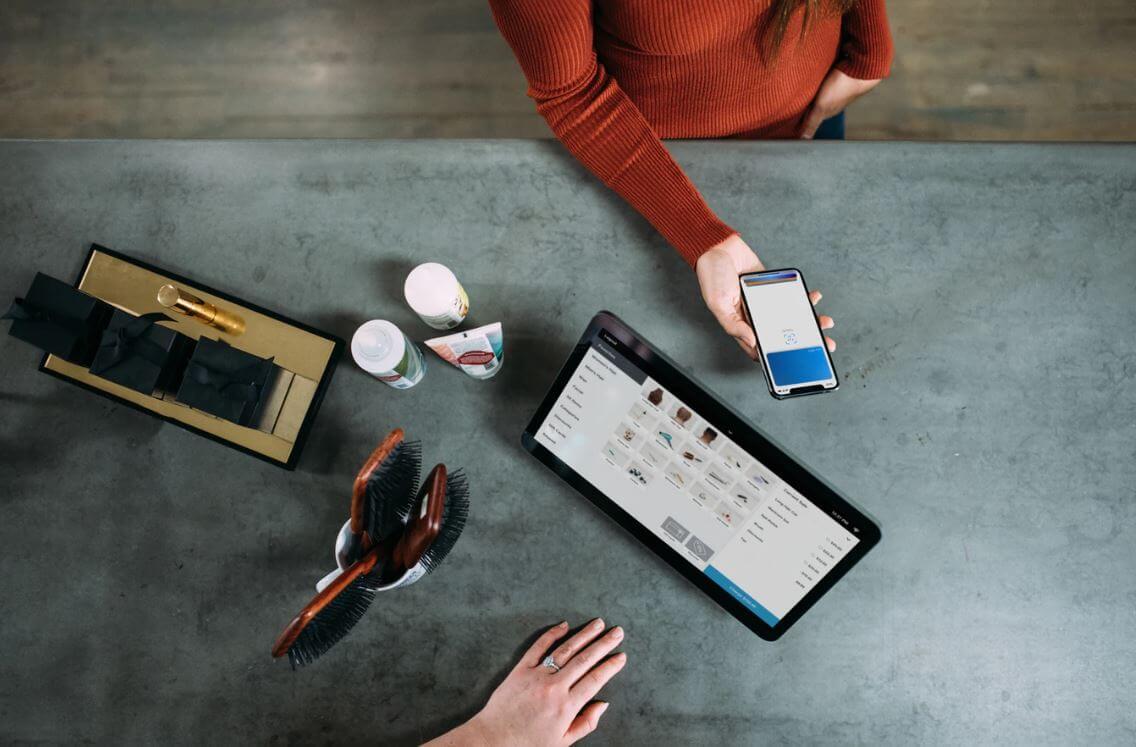 Loja virtual no Facebook: imagem de duas pessoas sob uma mesa, uma pessoa está segurando o celular e a outra está com a mão apoiada na mesa. Nas mesa tem um tablet com a página de uma loja virtual aberta e uma máquina de cartão.