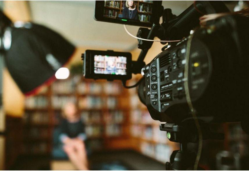 Ideias de videos para gravar: imagem de uma sala com uma câmera filmadora, uma luminária e uma mulher sentada ao fundo desfocada.
