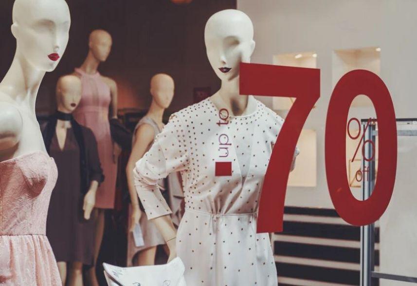 Marketing para loja de roupas: imagem de uma vitrine de loja com vários manequins dentro da loja e e um texto de 70% de desconto escrito no vidro de tinha vermelha .