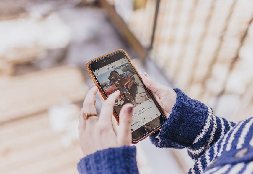 Como marcar pessoas no Instagram: imagem de uma mulher segurando o celular com uma mão e com a outra mão tocando na tela do Instagram