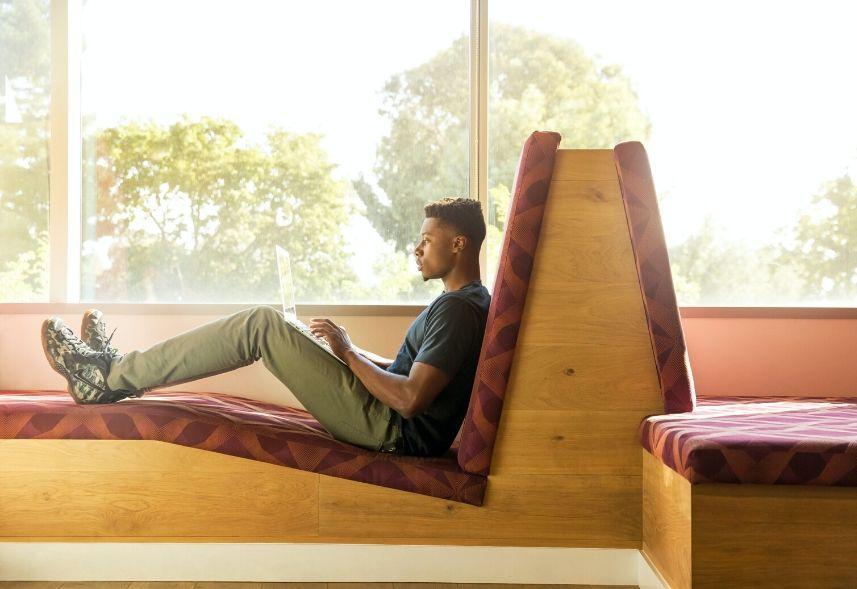 Recomendações no LinkedIn: imagem de um homem sentado num sofá com um notebook no colo digitando