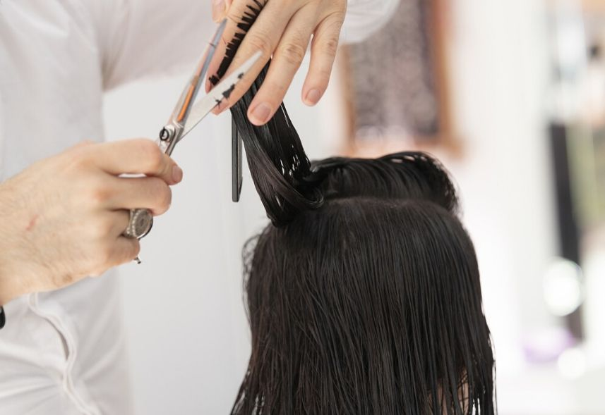 Redes sociais para salão de beleza: imagem de um homem cortando o cabelo de uma mulher com uma tesoura