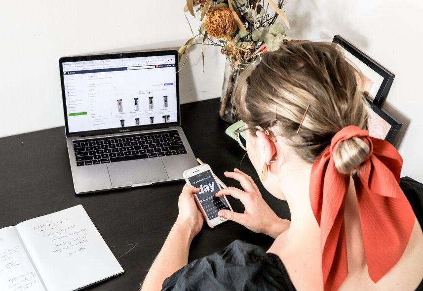 Como vender roupas pelo Instagram: imagem de uma mulher mexendo no celular com o notebook aberto em cima da mesa com imagens de roupas