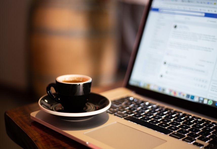 Ultimas novidades do Facebook: imagem de um notebook aberto com a página do Facebook na tela e uma xícara de café