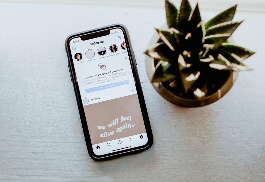Novidades do Instagram: imagem de um celular com a tela do instagram aberta, em cima de uma mesa branca ao lado de uma planta suculenta