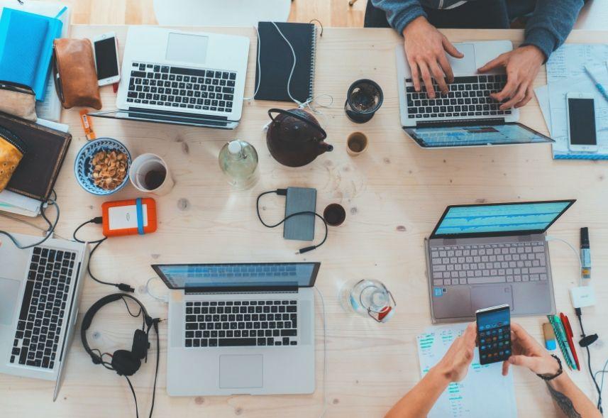 Social Ads: imagem de uma mesa de trabalho com quatro notebooks abertos duas pessoas trabalhando
