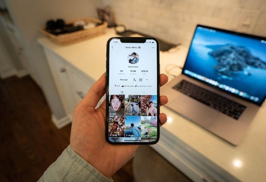 TikTok Marketing: imagem de uma mão de homem segurando um celular com a tela aberta no TikTok
