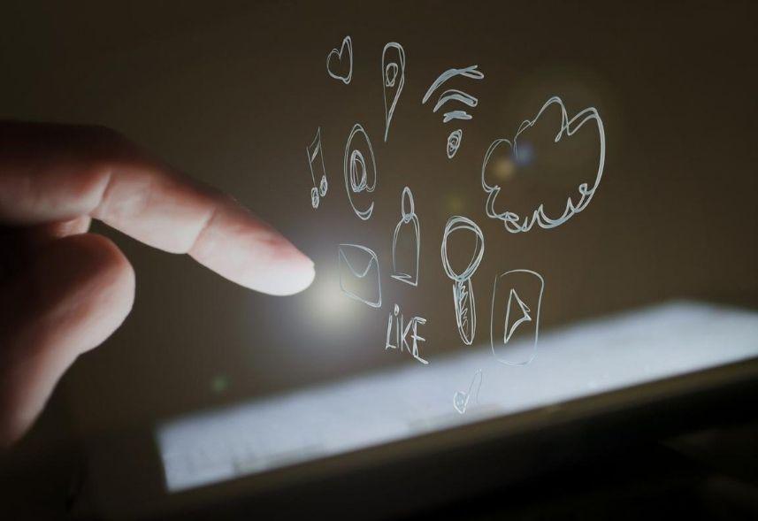 Social commerce: imagem de um dedo em direção a tela de um celular com ícones de wifi, nuvem, arroba e curtidas saindo da tela.