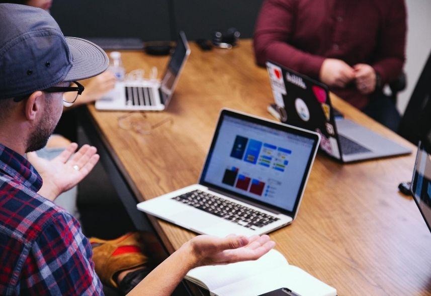 Relatório Stories Instagram: imagem de uma reunião com três pessoas uma mesa de madeira e três notebooks, um homem está em destaque usando uma camisa xadrez e boné
