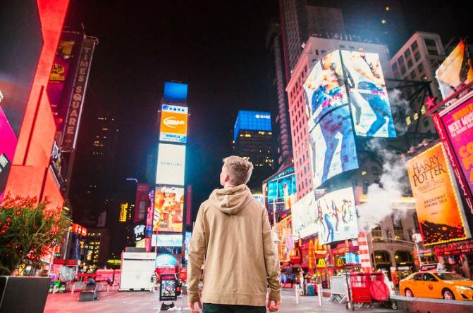 como aparecer no explorar do instagram: imagem de um jovem no meio da rua olhado para vários outdoors e vitrines
