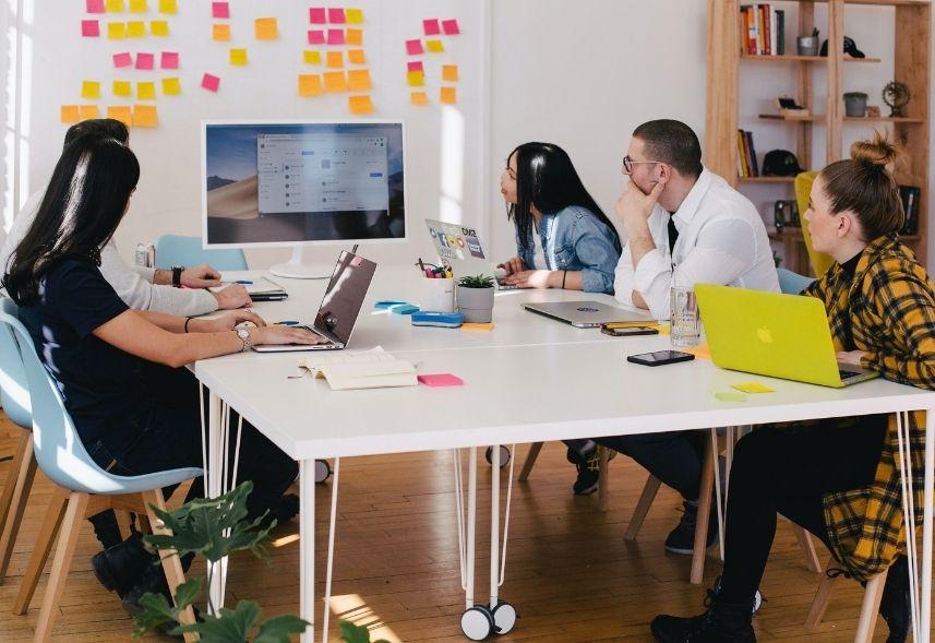 Plano de marketing digital: imagem de uma sala de reunião com várias pessoas sentadas conversando sobre negócios olhando para uma parede de post it coloridos