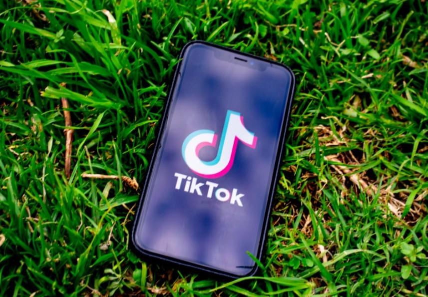 """Ganhar Seguidores no TikTok header: Um celular está jogado no gramado, em sua tela é possível ler """"TikTok""""."""