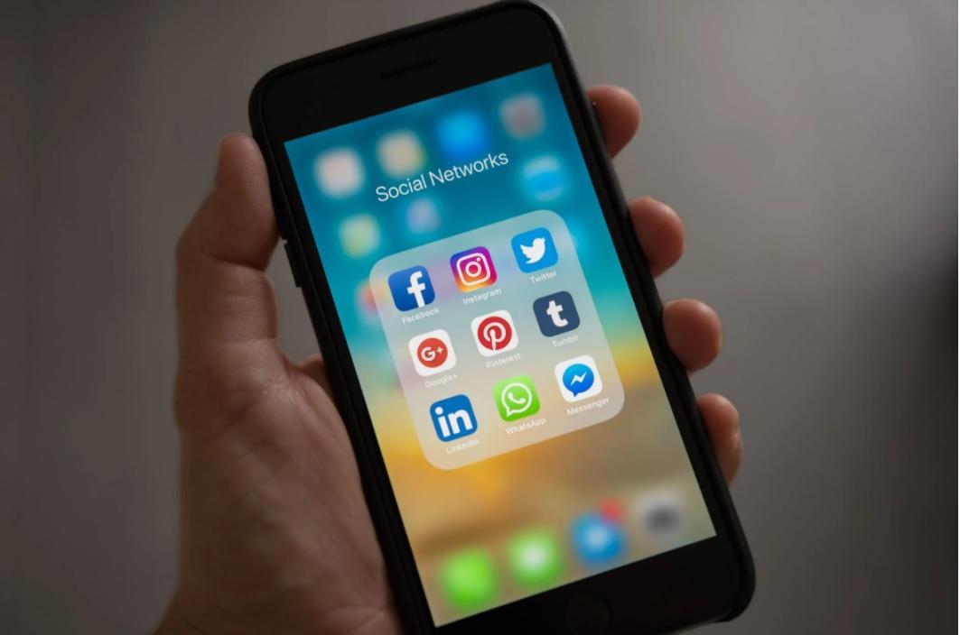 mobile first: uma mão segura um celular e dentro da tela é possível ver atalhos de aplicativos de redes sociais como Facebook, Instagram, Twitter e tumblr.