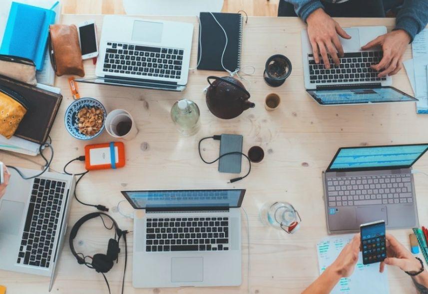 conteudo_hero_hub_e_help: a imagem é uma foto tirada de cima de uma mesa, nela estão espalhados 4 computadores abertos, alguns celulares. Aparecem duas pessoas, apenas suas mãos à mostra. Uma está usando o computador, outra está usando o celular.