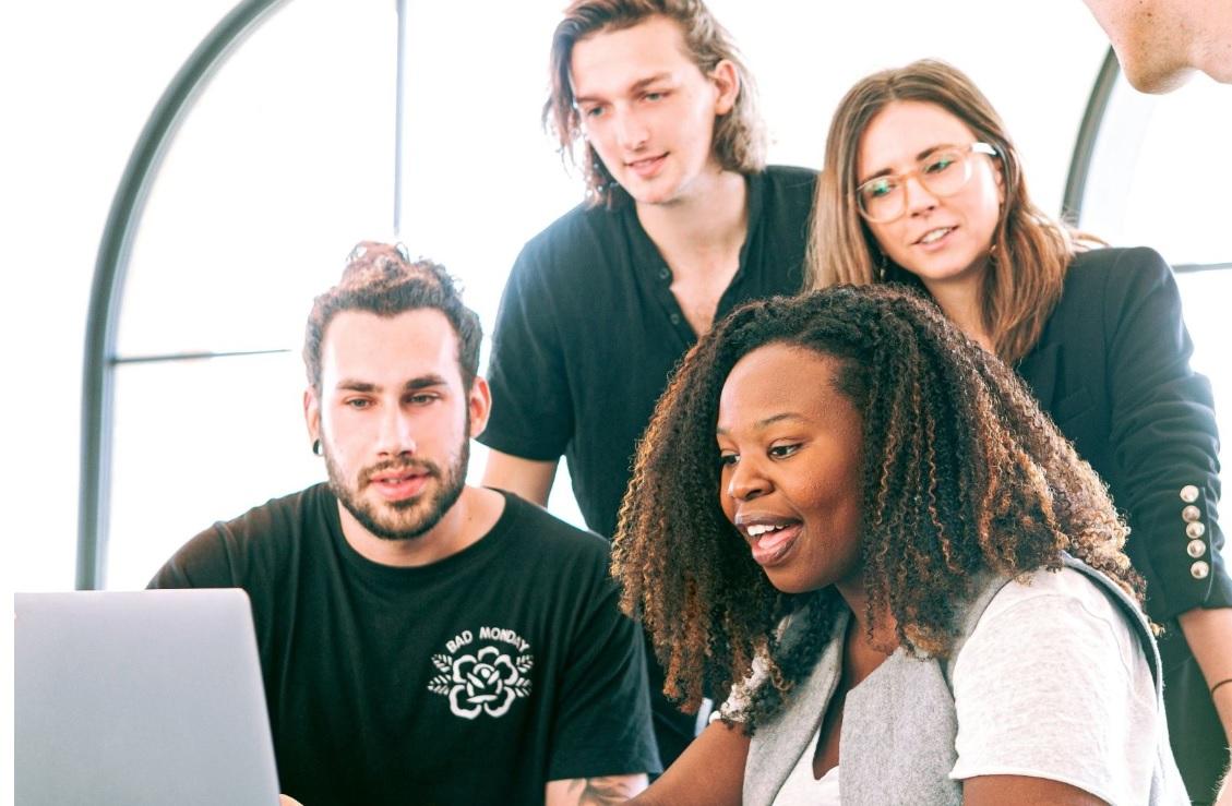 Marketing de comunidade: Um grupo de pessoas estão acompanhando uma moça negra que apresenta algo na tela de um computador.
