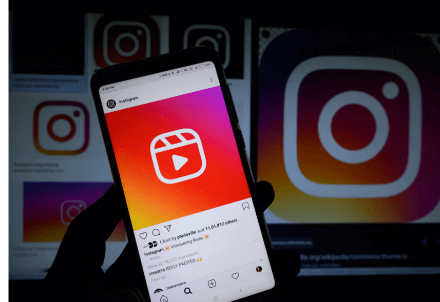 Instagram reels: imagem de uma mão segurando um celular com a tela mostrando um post reels do Instagram