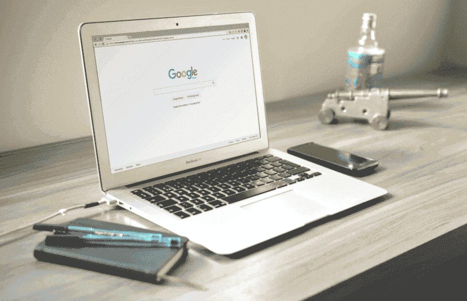 Como anunciar no Google Ads: em uma mesa, estão dispostos um caderno com canetas e um computador. A tela do computador está ligada na página de busca do Google, dando para ver a logo colorida em vermelho, amarelo, verde e azul da empresa.