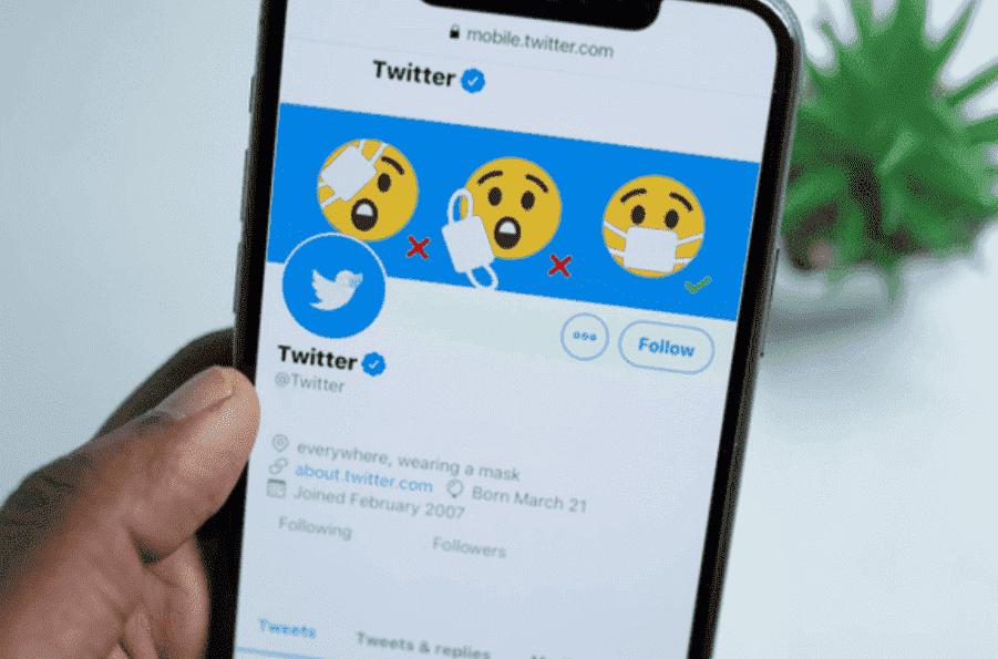 Capa para Twitter header: uma mão branca está segurando um celular ligado na página principal do Twitter, no qual podemos ver a foto da capa e do perfil.