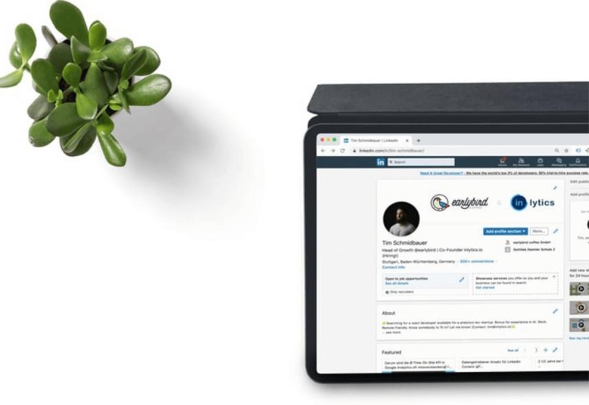 grupos no linkedin: imagem de um notebook com a tela do linkedin aberta em cima de uma mesa branca ao lado de um vaso de planta