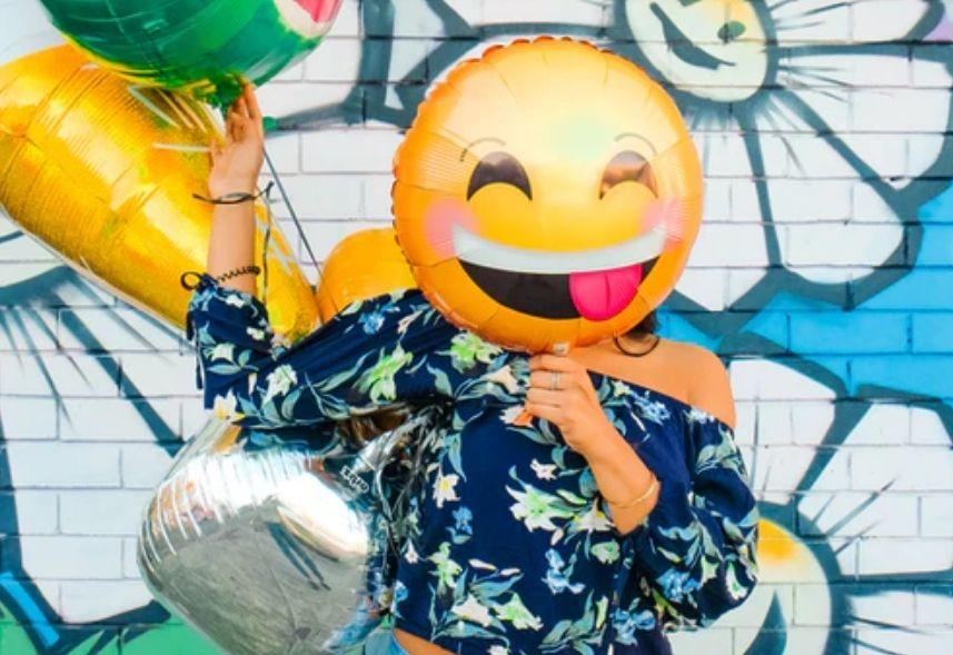 Cupom mLabs: imagem de uma mulher segurando um balão de emoji na frente do seu rosto e outros balões coloridos na outra mão