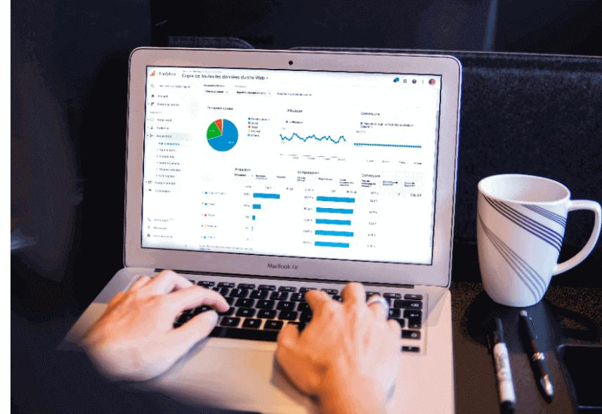 taxa de rejeicao google analytics: imagem de duas mãos digitando no teclado de um notebook com a página do Google Analytics aparecendo na tela
