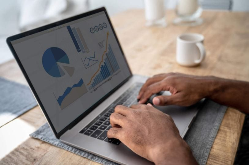criar conta no google analytics: imagem de duas mãos masculinas digitando em um notebook sobre a mesa com gráficos aparecendo na tela