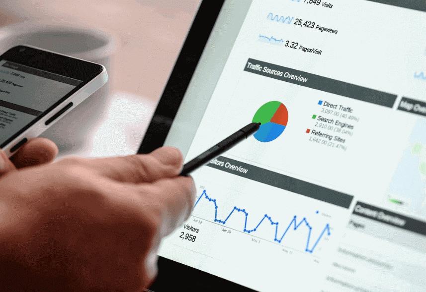 o que e google analytics: imagem de uma mão segurando uma caneta apontando para a tela de um notebook com imagens de gráficos aparecendo no monitor