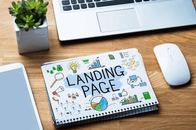Criar landing page: imagem de uma página de caderno, escrito landing page, sob uma mesa de madeira ao lado de um notebook e uma planta