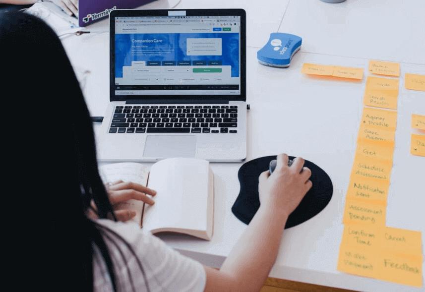 Thank You Page: imagem de uma mulher no computador usando o mouse. Na tela, aparece uma página azul.