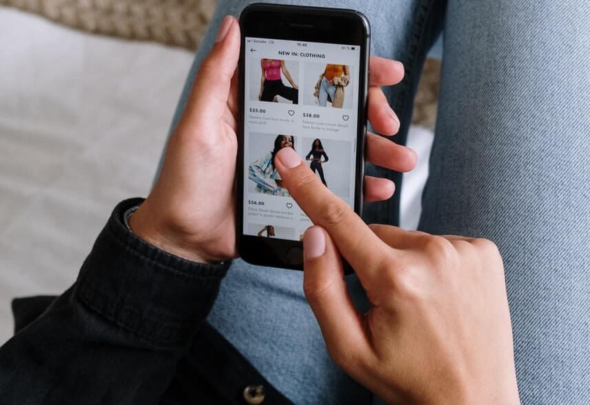 Google Shopping: imagem de uma pessoa usando o celular. Na tela, aparece uma página de compra de roupas.