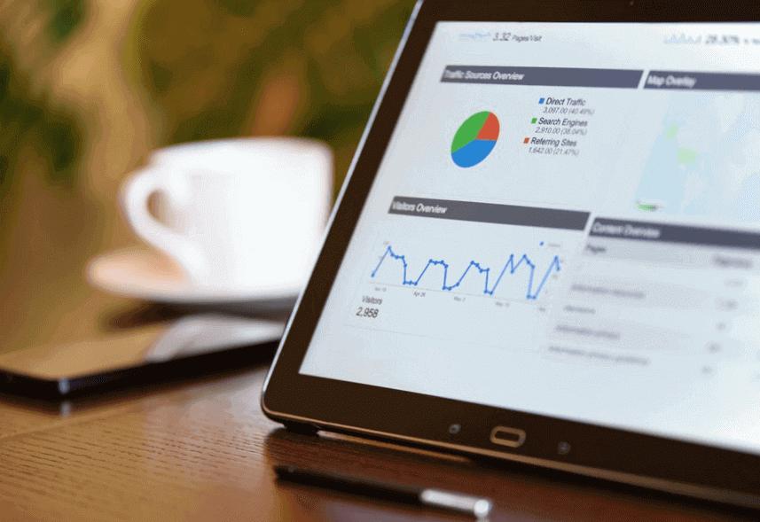 Relatório Google Analytics: imagem da tela de um computador com gráficos do Google Analytics. Ao fundo, há uma xícara e um celular.