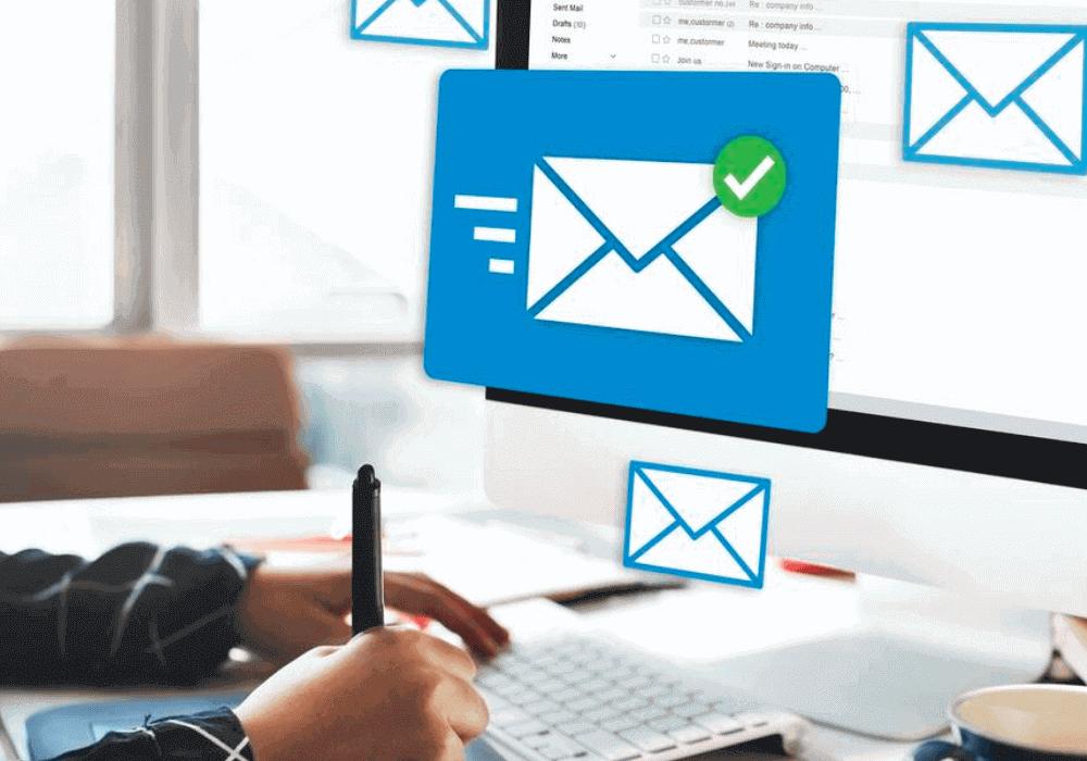 Ferramenta de email marketing: imagem de uma pessoa na frente do computador usando uma caneta. Grandes ícones de e-mail saem da tela.