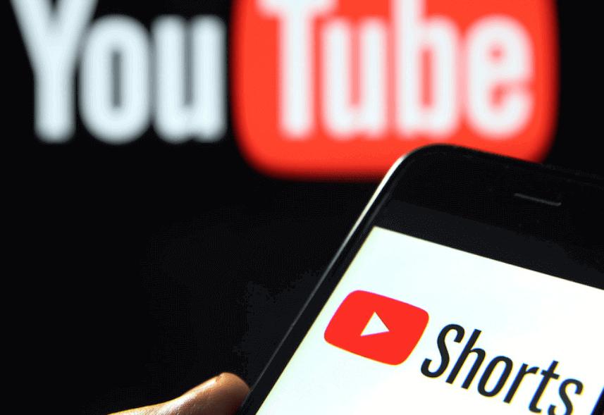 YouTube Shorts: a imagem mostra a tela de um celular com o logotipo do Shorts. Há também o ícone do YouTube como pano de fundo.